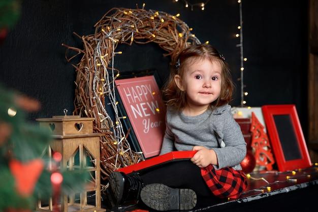 축제 나무와 갈 랜드 근처에 앉아 어린 소녀