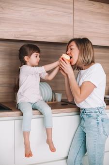 부엌 표면에 앉아있는 어린 소녀, 그녀의 어머니가 사과를 물도록주는