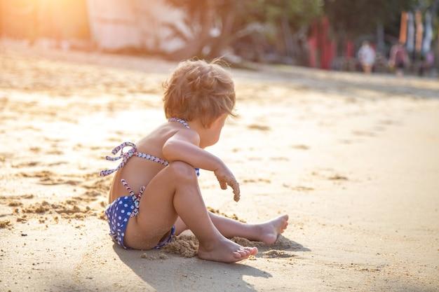 Маленькая девочка сидит на песчаном пляже на солнце