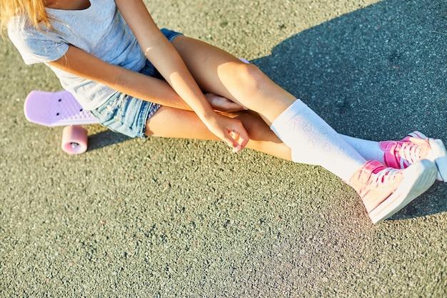 스케이트보드에 앉아 있는 어린 소녀, 흰색 양말과 분홍색 신발을 신은 익명의 아이가 여름 도시의 시골 거리에서 스케이트보드를 타고 있습니다.
