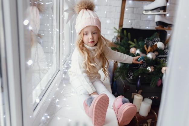 크리스마스 아침에 창틀에 앉아 어린 소녀.