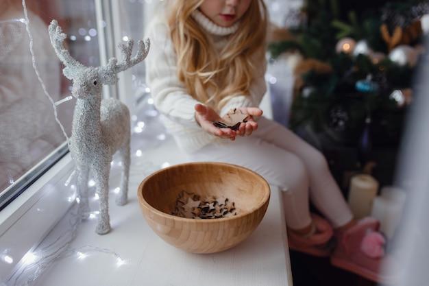 Маленькая девочка сидит на подоконнике в рождественское утро.