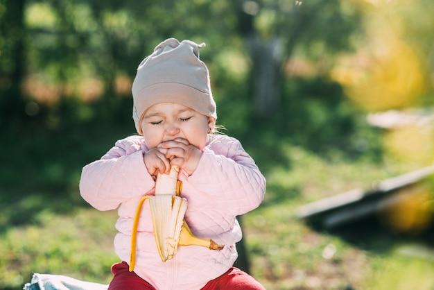 Маленькая девочка сидит на деревянной бочке и ест банан в саду