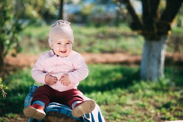 Маленькая девочка сидит на деревянной бочке в саду в деревне со своей бабушкой