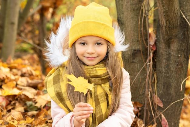 森の中の秋の落ち葉に座っている少女。