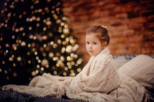 침대에 앉아 어린 소녀는 갈색 벽돌 벽과 새 해 나무 앞에 흰색 격자 무늬에 싸여 카메라를보고 나뭇잎 화환 조명이 있습니다. 로프트 스타일의 인테리어. 공간 복사