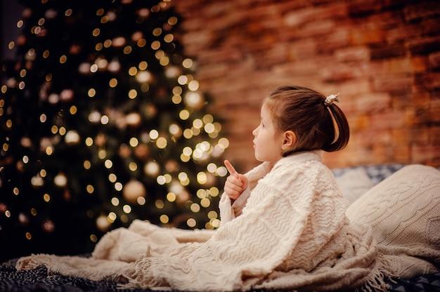 갈색 벽돌 벽과 새 해 나무 앞의 흰색 격자 무늬에 침대에 앉아있는 어린 소녀가 손가락으로 나타나는 나뭇잎 화환 조명과 함께. 로프트 스타일의 인테리어. 공간 복사