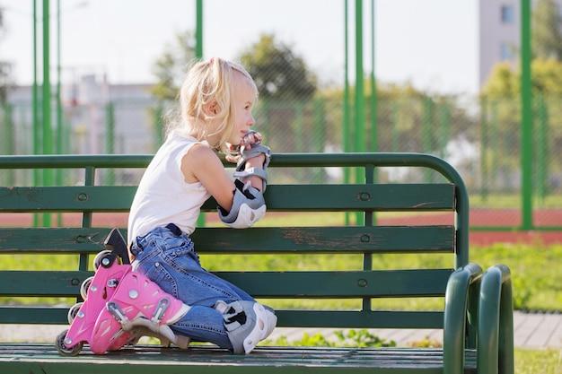 Маленькая девочка сидит на скамейке на детской площадке в роликовых коньках