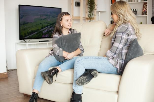 ふわふわの枕を持ってソファに座って母親と会話をしている少女。