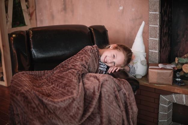 집에서 아침에 크리스마스 트리 근처 아늑한 의자에 앉아 어린 소녀.