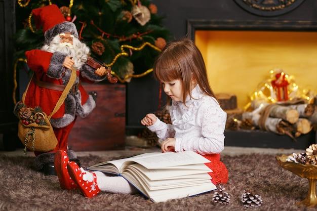 Маленькая девочка сидит на полу в красивых рождественских украшениях. девушка читает сказочную игрушку деда мороза. девушка играет с игрушкой дед мороз.