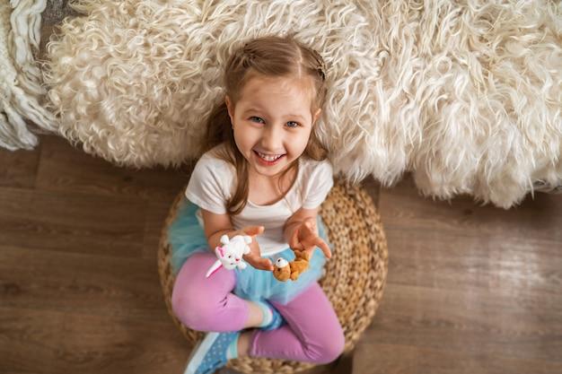 어린 소녀는 소파에 기대어 바닥에 앉아 손가락 장난감을 가지고 노는 재미