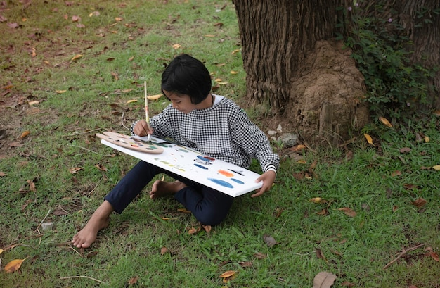 緑の芝生の1階に座って、キャンバスに色を塗る少女。幸せな気持ちで、良い趣味、公園で