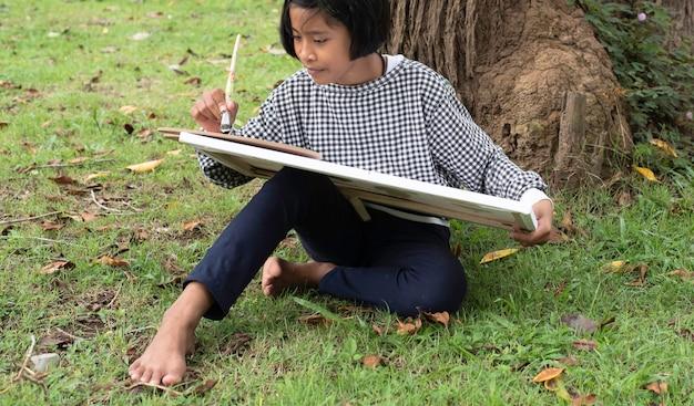 Маленькая девочка сидит на первом этаже зеленой травы, рисует цвет на холсте. с интересом, в парке