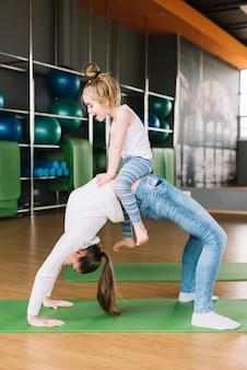 Маленькая девочка сидит на животе своей матери во время занятий в тренажерном зале