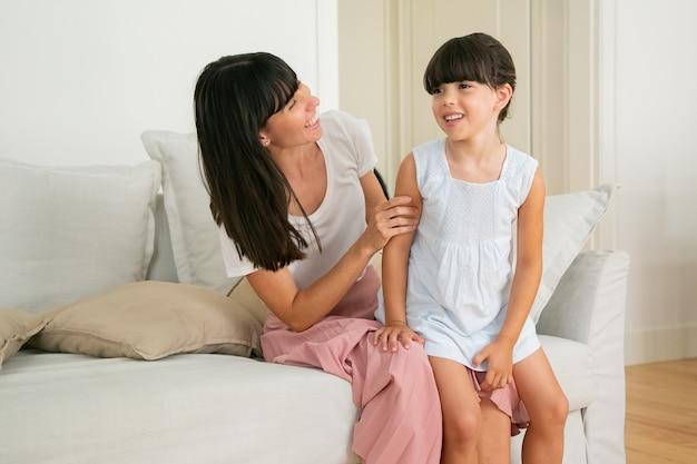 ママの膝の上に座って、笑顔でリビングルームで話している小さな女の子。