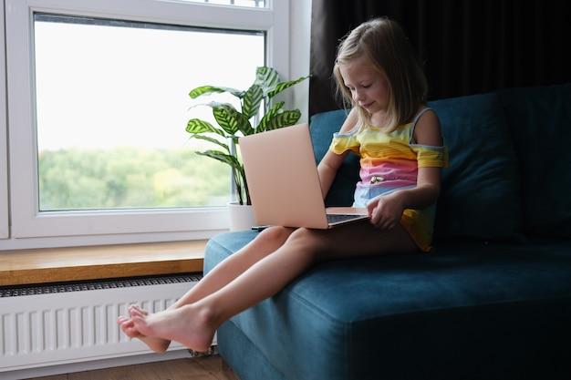 Маленькая девочка сидит на диване с ноутбуком на коленях