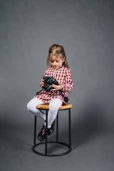 Little girl sitting on stool looking at camera against gray background
