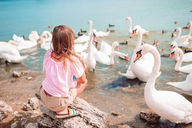 Маленькая девочка сидит на пляже с лебедями