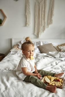 침실에있는 침대에 앉아 치즈 한 조각을 먹는 어린 소녀.