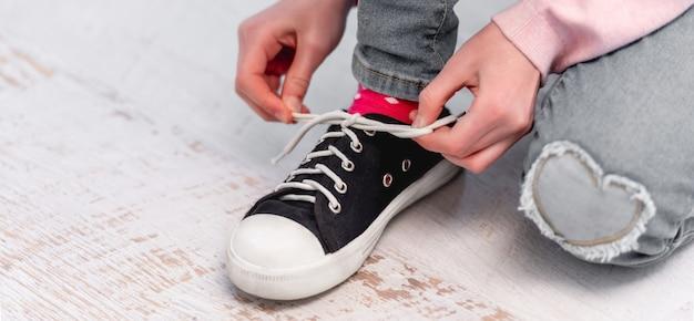 床に座って、黒と白の色のスナイカーに靴紐を結ぶ少女