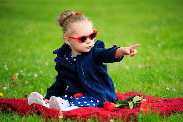 サングラスをかけて公園の芝生に座っている少女
