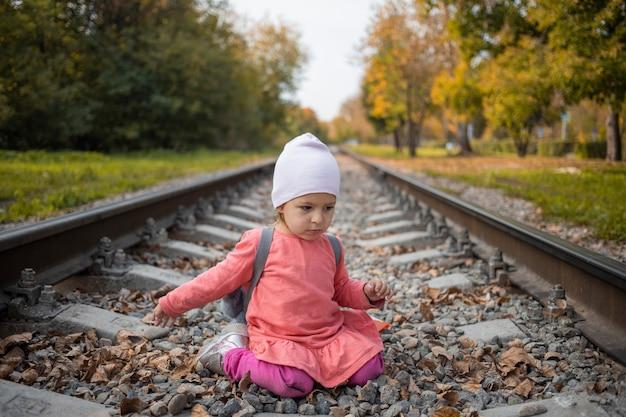 철도 트랙에 앉아 어린 소녀입니다. 숲에서 철도에서 노는 유아