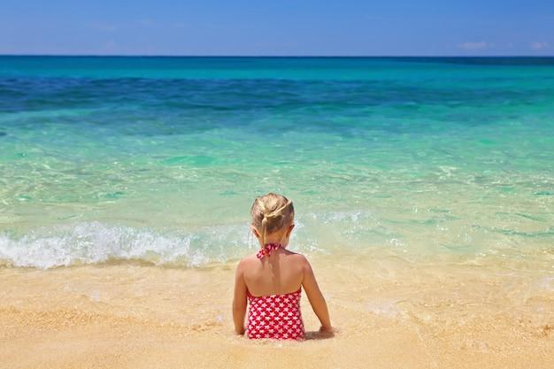 모래 해변에 앉아 어린 소녀는 푸른 바다를 본다