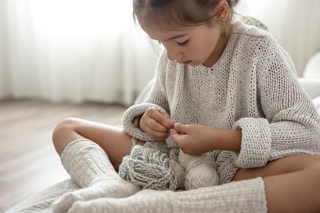 Маленькая девочка сидит на диване и учится вязать, концепция домашнего досуга.