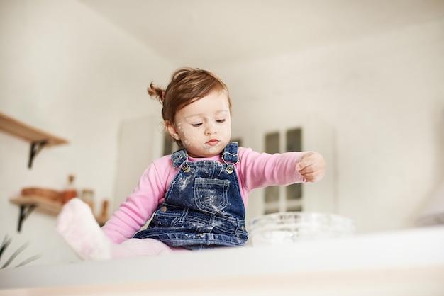 テーブルの上に座って、皿に小麦粉を注ぐ少女