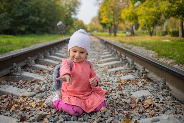 숲에서 기차 트랙에 앉아 어린 소녀