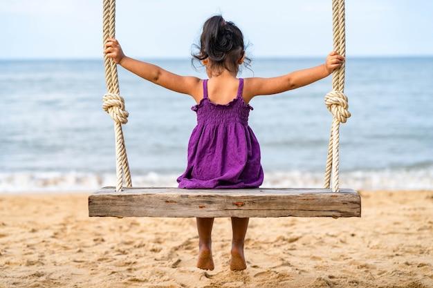 Маленькая девочка сидит на деревянных качелях на пляже.