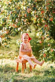 체리 필드 배경에서 나무 의자에 앉아 어린 소녀