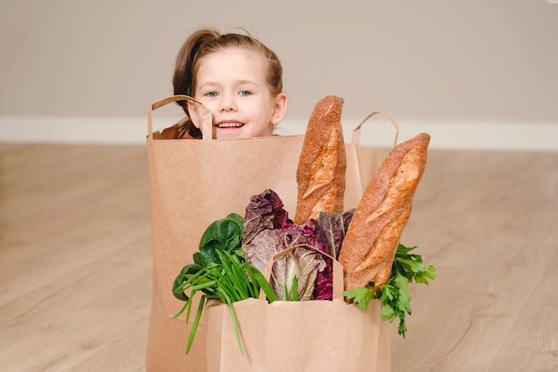 Little girl sitting in paper bag hiding with vegetables and bread, grocery with copy space