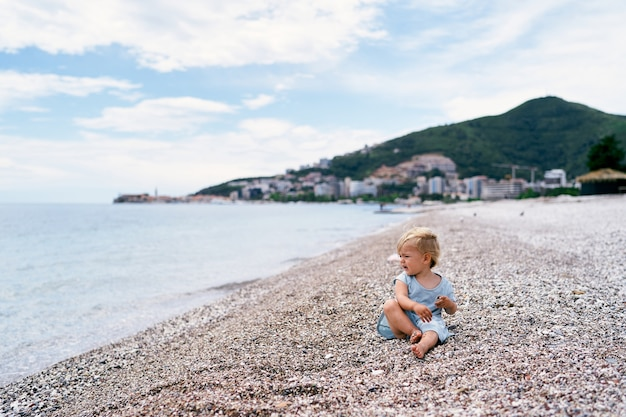 Little girl sitting on a pebble beach and looking at the sea