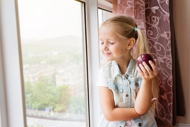 Little girl sitting on the sill at home, looking in window and holding red apple
