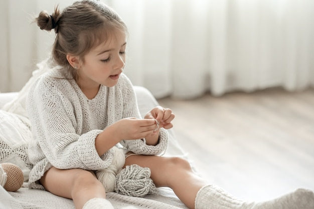 Little girl sitting on the sofa and learning to knit, home leisure concept.