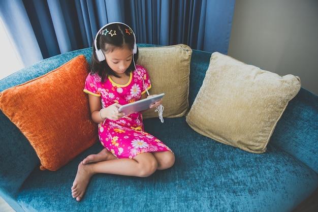 Little girl sitting on sofa listening music from headphone computer tablet