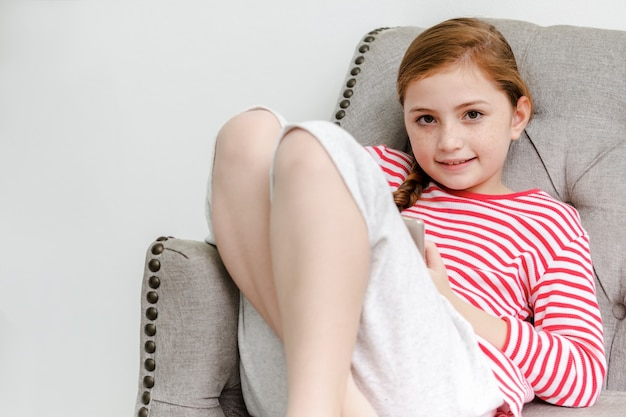 Little girl sitting on sofa play smartphone in living room