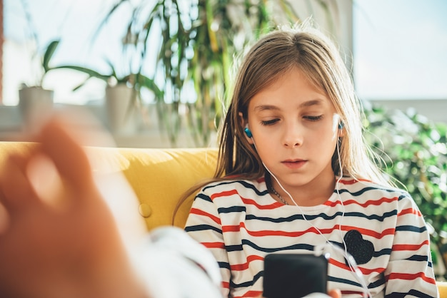 Little girl sitting on sofa and using smart phone