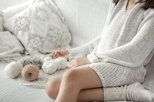 Little girl sitting on the sofa with threads, home leisure concept, knitting.