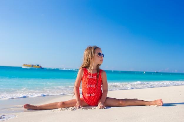 Little girl sitting on the splits at white sandy beach