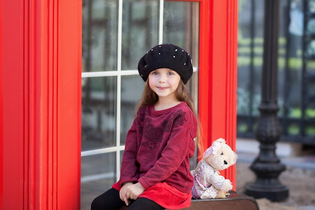 Little girl sitting on a suitcase with a teddy bear. london red telephone booth. spring. autumn. with the international women's day. since march 8! close-up portrait of the face little girl child.