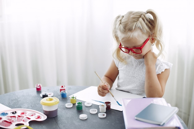 Little girl sitting on a table and drawing