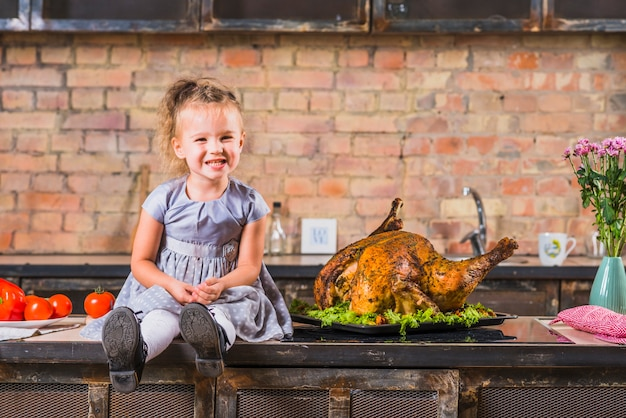 Little girl sitting on table with roasted turkey