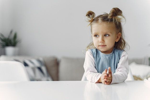 Little girl sitting on a table with toy
