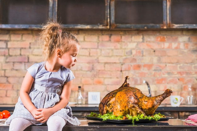 Little girl sitting on table with turkey