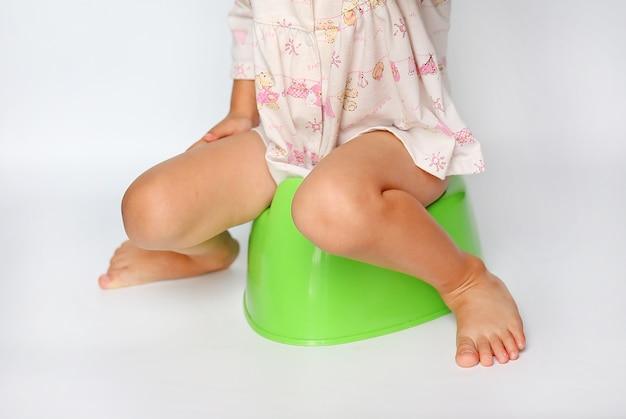 Little girl sitting on toilet training potty on white background