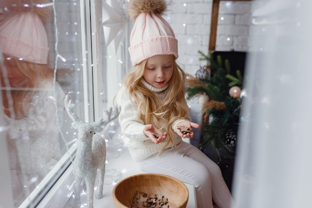 Little girl sitting on a window sill in christmas morning.