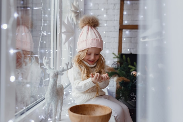 Little girl sitting on a window sill in christmas morning